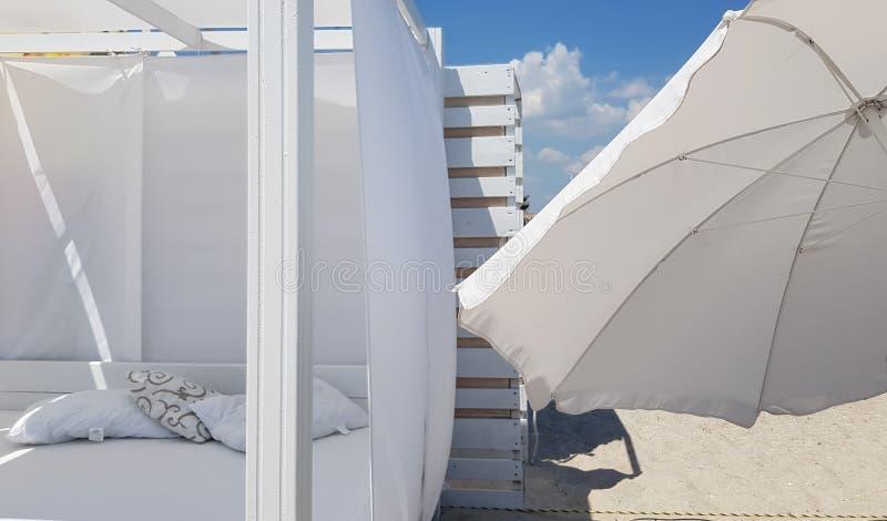 Parasole e parasole bianchi sulla chiara sabbia della spiaggia immagine stock
