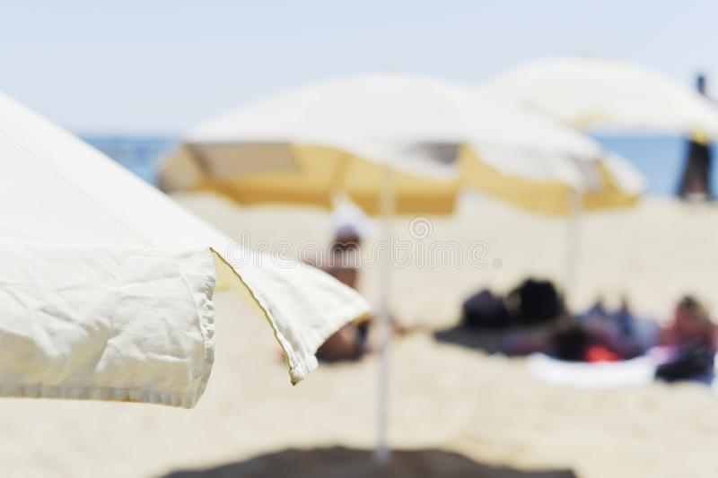 Parasole i ludzie sunbathing w plaży zdjęcie royalty free