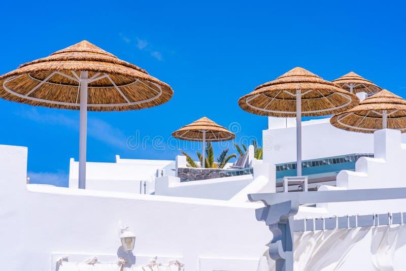 Parasoles außerhalb der traditionellen rehabilitierten Häuser auf griechischer Insel von Santorini lizenzfreie stockfotos