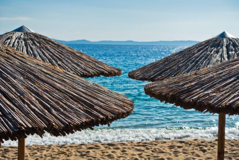 Parasoles de la paja en una playa en Sithonia fotografía de archivo