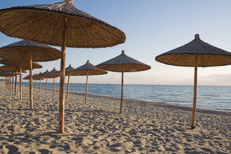 Parasoles de playa de la paja fotos de archivo