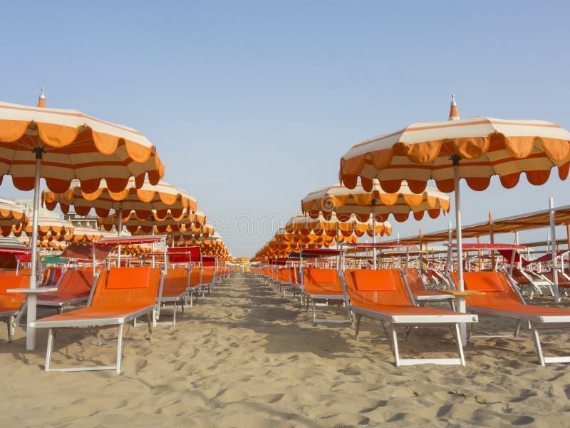 Parasoles de playa, gazebos y camas del sol en las playas arenosas italianas Región adriática de Emilia Romagna de la costa imagen de archivo