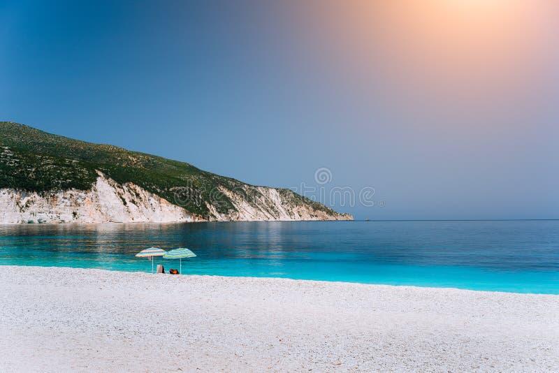 Parasoles de playa de Sun en un Pebble Beach con el mar tranquilo azul azul, las rocas blancas y el cielo claro en fondo fotos de archivo libres de regalías