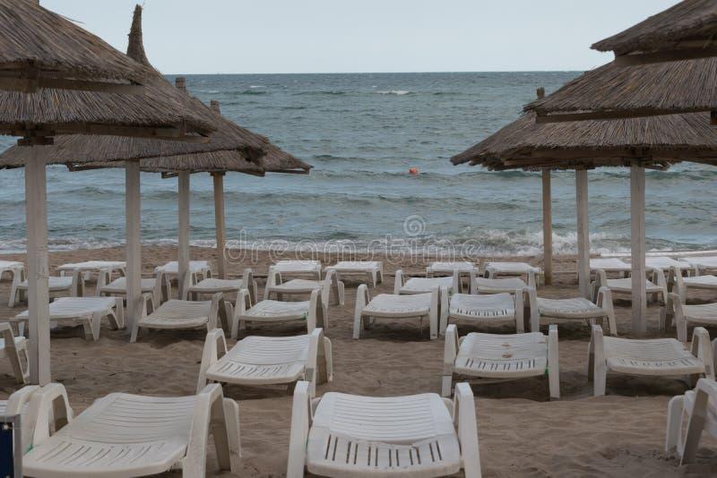 Parasoles de playa, sunbeds vacíos y sillones en la playa en la playa rumana en Neptun, Constanta Rumania imagen de archivo