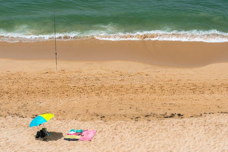 Parasoles de Sun y una caña de pescar en una playa soleada en Portugal imagen de archivo libre de regalías