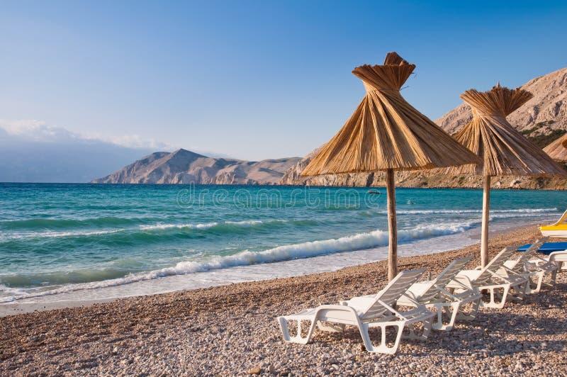Parasoll och solstol på strand på Baska i Krk Kroatien arkivfoton