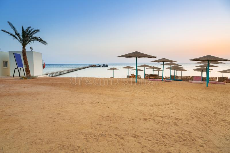 Parasols on the beach of Red Sea in Hurghada at sunrise stock images
