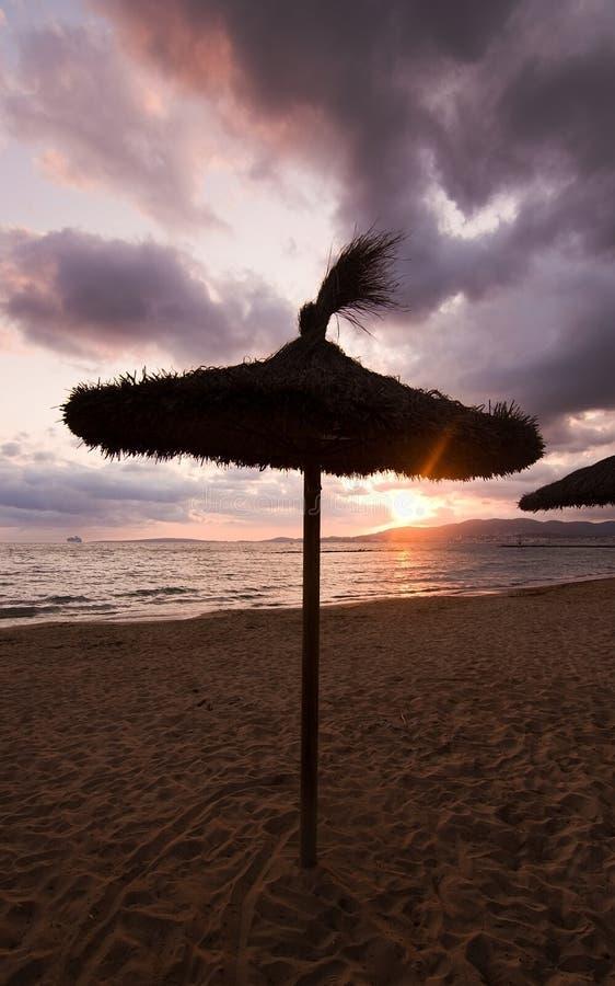 Parasols de plage de coucher du soleil photographie stock