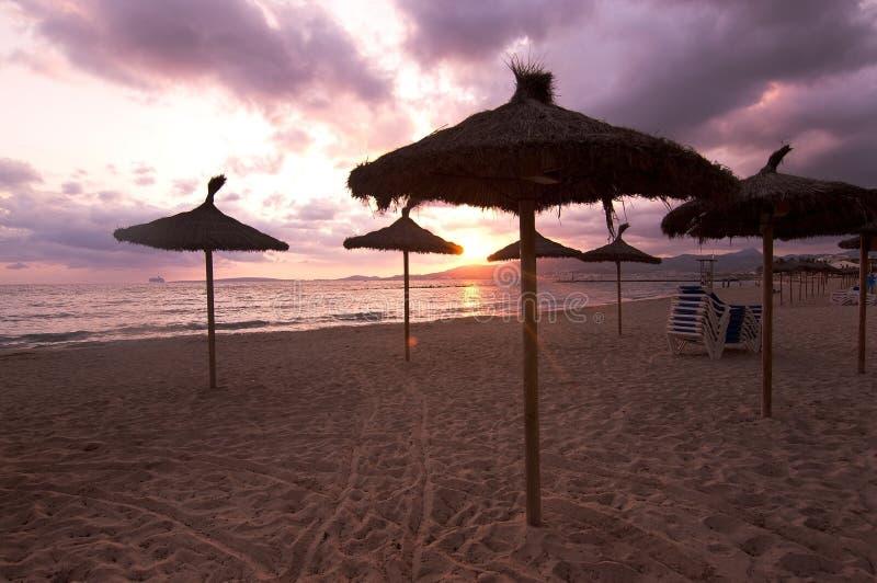 Parasols de plage de coucher du soleil images stock
