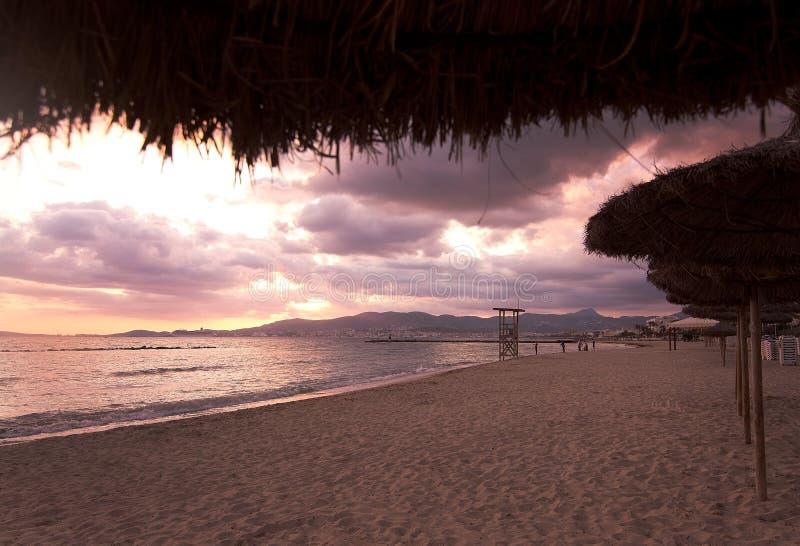 Parasols de plage de coucher du soleil images libres de droits
