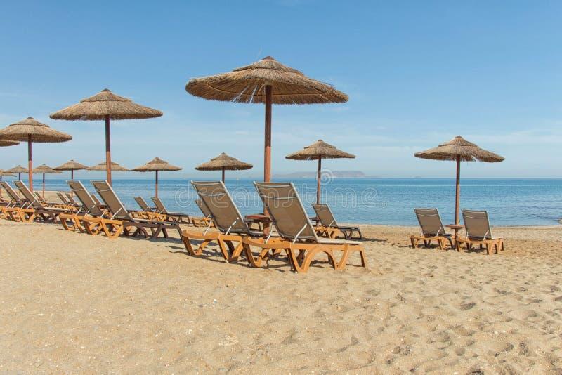 Parasols et canapés du soleil sur la plage photo stock
