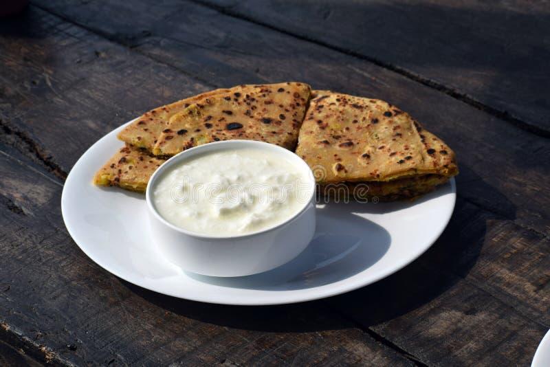 Paratha et lait caillé d'Aloo pour le petit déjeuner placé sur le conseil en bois photographie stock libre de droits
