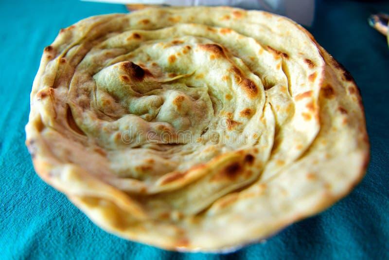 Paratha, okrągły łuskany chleb indyjski z całej pszenicy, selektywna koncentracja, zbliżenie Laacha paratha w restauracji tradycy zdjęcie stock
