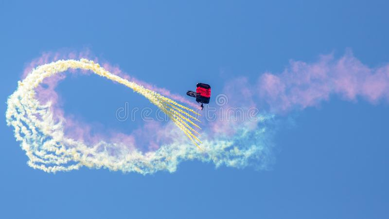 Paratrooper of United States Army Special Operations Command, USASOC. Gliding down with colorful smoke at Hillsboro International Airshow royalty free stock photos