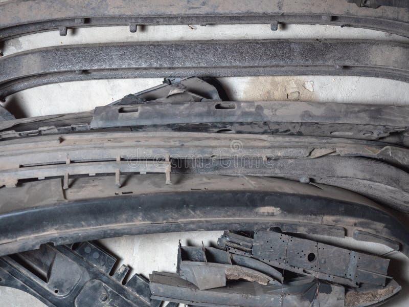 Paraurti tagliati i vecchi di un'automobile del veicolo hanno accatastato insieme vicino alla parete sporca del veicolo balzata F fotografie stock