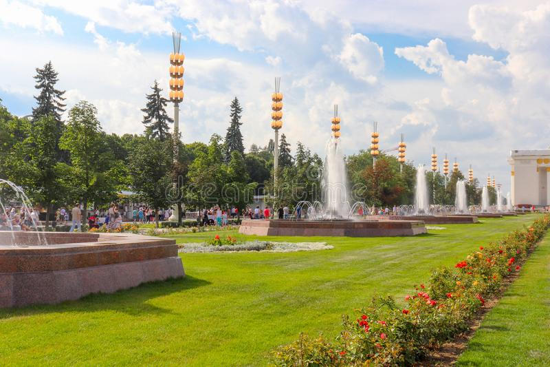 Parc d'été avec des fontaines et de grandes lanternes Une pelouse verte avec de belles fleurs images libres de droits
