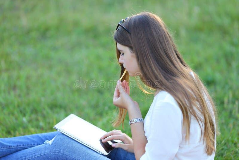 Parc de Famale et ordinateur portable se reposants de travaux mangeant des aliments de préparation rapide photographie stock libre de droits
