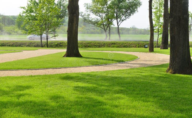 Parc de région boisée avec des pelouses manicured et une route photographie stock libre de droits