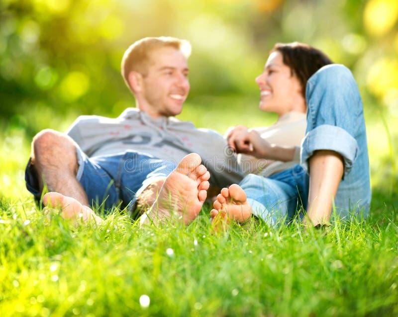 Jeunes couples se trouvant sur l'herbe photos stock