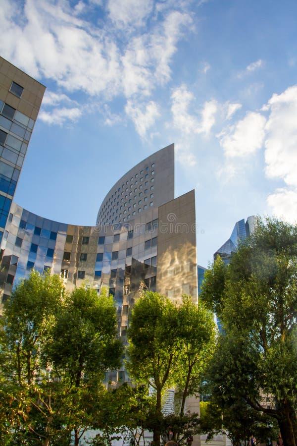 Parc vert à côté de hauts gratte-ciel en hausse en verre modernes et de backgroundin de ciel bleu le secteur de la défense de La  photo stock