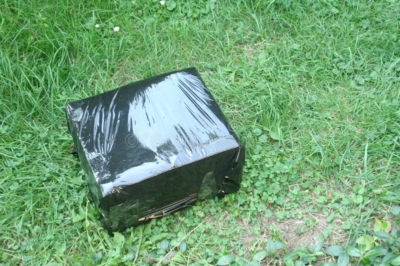 Parcel in a black box lying on the grass. Curier posts. Receiving parcels. A parcel in a black box lying on the grass. Curier posts. Receiving parcels stock images