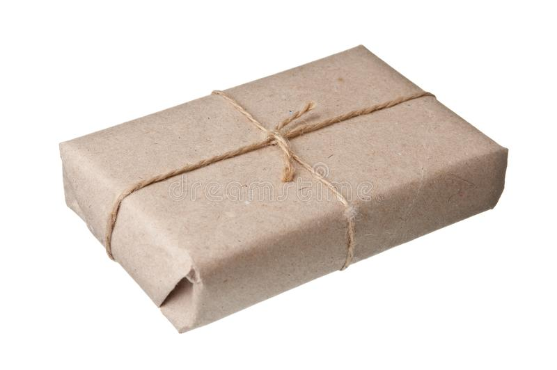 Parcel wrapped with brown kraft paper. Isolated on white background royalty free stock photo