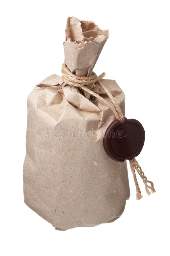 Parcel wrapped  with a wax seal. Parcel wrapped with brown kraft paper with a wax seal isolated on white background royalty free stock photography