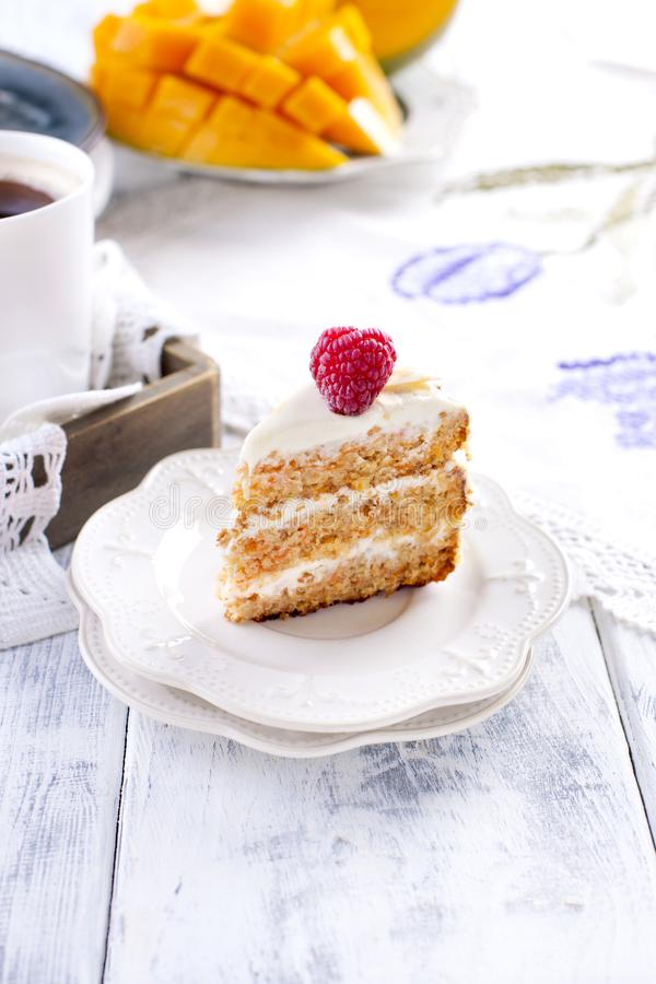 Parcela de bolo em uma placa branca pequena, com um creme para o fruto da manga do café da manhã A Fundo branco, xícara de café e imagens de stock royalty free