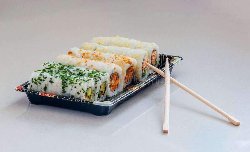 Parcela de diversos tipos do sushi na bandeja e nos hashis fotografia de stock