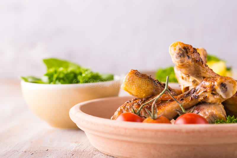 Parcela de poucos pés de galinha na placa na frente das batatas e da salada verde imagens de stock