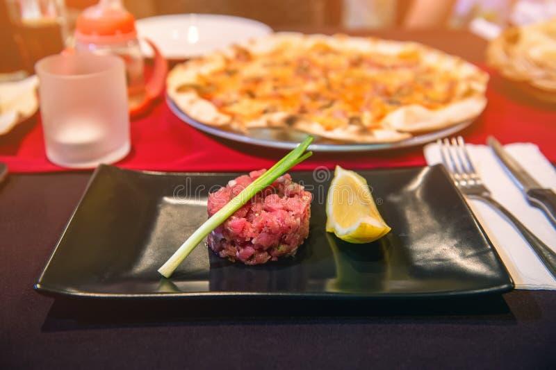 Parcela de sua carne tartare com as cunhas de limão na placa preta na tabela no café foto de stock royalty free