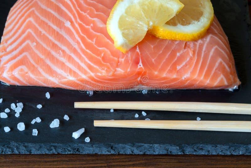 Parcela deliciosa de faixa salmon fresca com limão, sal, woode fotos de stock