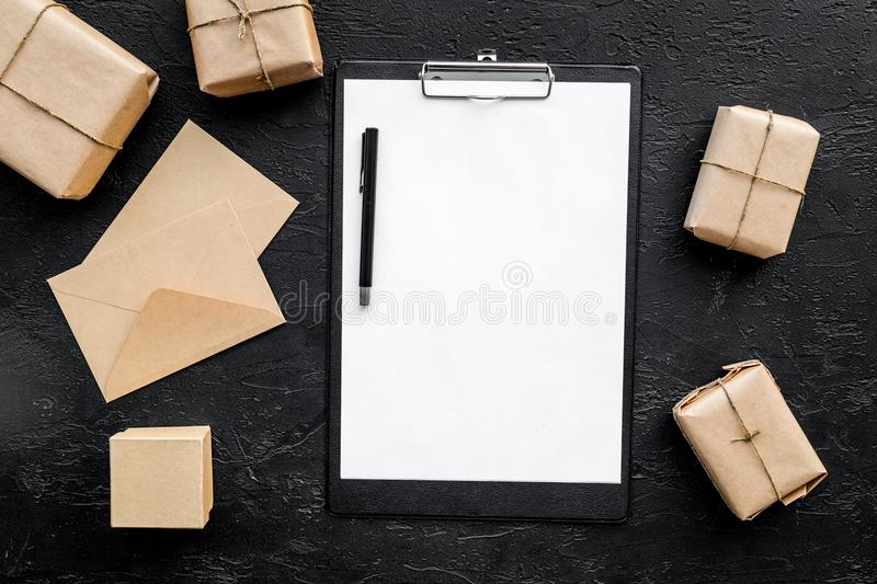 Parcels box and envelope in delivery service office black background top view space for text royalty free stock image