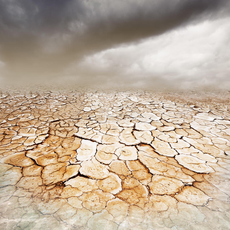 Parched earth. Dry, parched cracked earth with stormy dusty sky and foreground water royalty free stock photo