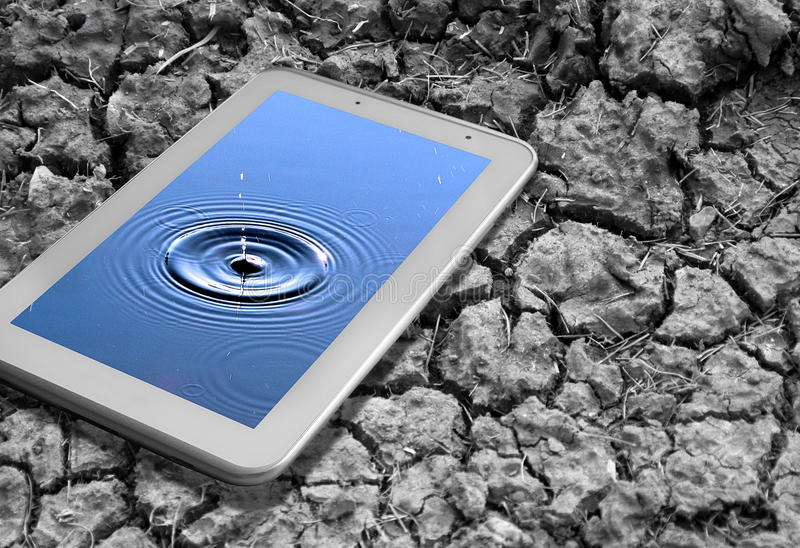 Parched earth global solutions. Conceptual photo of parched earth global solutions theme showing tablet device with water resting on dry ground royalty free stock photos