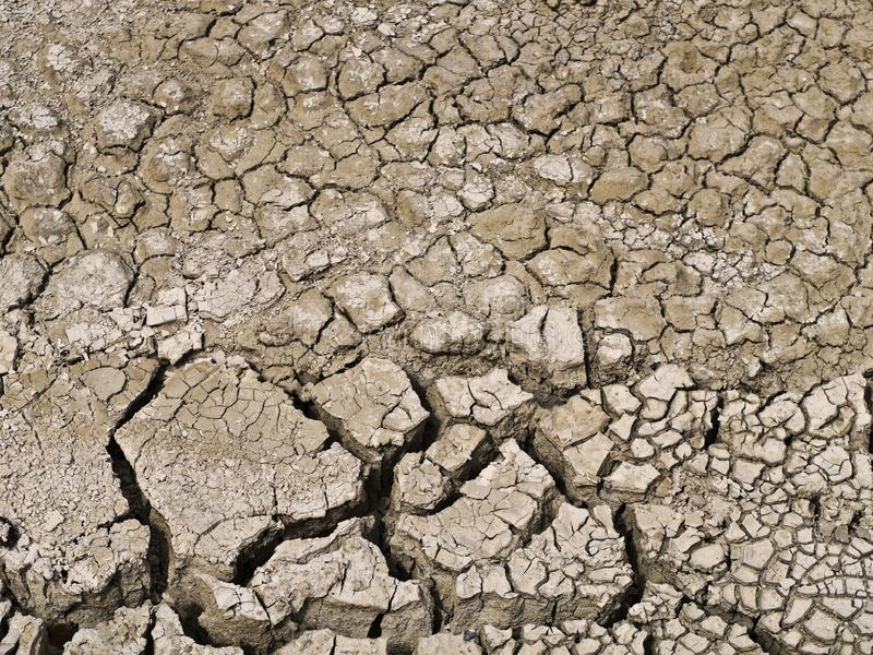 Parched earth macro. Dried out dehydrated parched earth sits baking in the sun reveals a deep crack effect in sepia.  water hydration land seasons drought empty royalty free stock photography