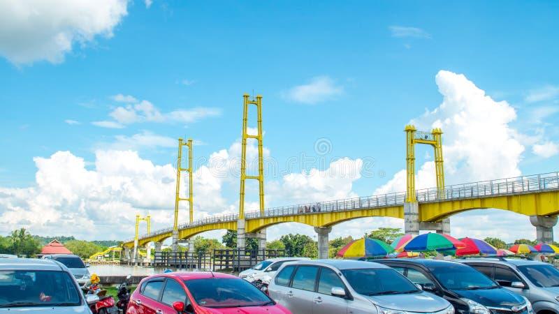 Parcheggio dell'automobile accanto al ponte pedonale in Pulau Kumala, Tenggarong, Indonesia fotografie stock