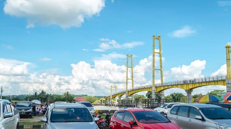 Parcheggio dell'automobile accanto al ponte pedonale in Pulau Kumala, Tenggarong, Indonesia immagini stock libere da diritti