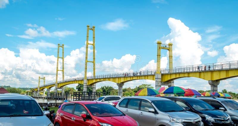 Parcheggio dell'automobile accanto al ponte pedonale in Pulau Kumala, Tenggarong, Indonesia immagini stock