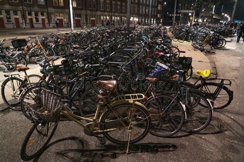 Parcheggio della bicicletta ammucchiato A di Amsterdam fuori della stazione centrale alla notte fotografia stock libera da diritti