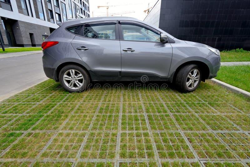 Parcheggio ecologico dell'automobile delle cellule e dell'erba concrete del tappeto erboso fotografie stock