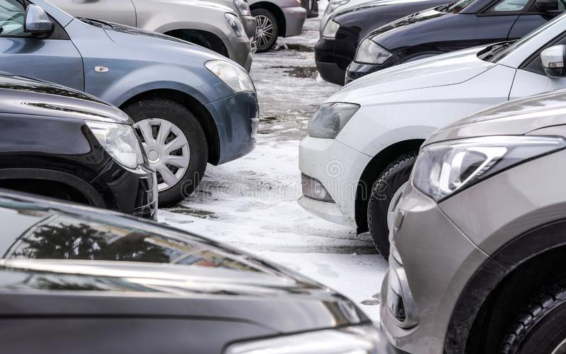 Parcheggio in parcheggio innevato, dettaglio sui fari del paraurti anteriore e gomme soltanto fotografie stock