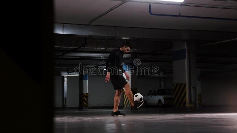 Parcheggio sotterraneo Un uomo di calcio che prepara le sue abilit? di calcio Equilibri la palla sui suoi piedi fotografia stock
