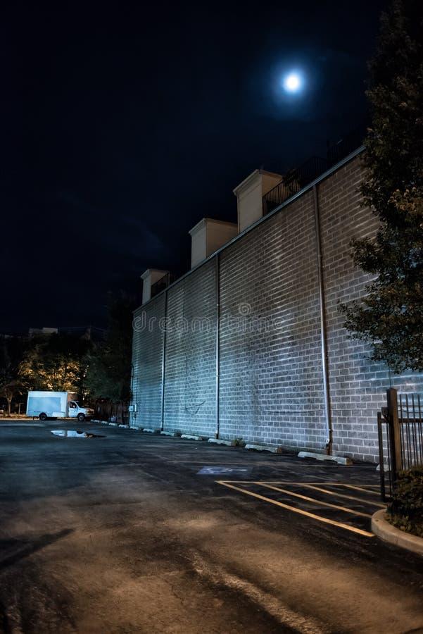 Parcheggio urbano del centro vuoto scuro e spaventoso della città alla notte fotografie stock