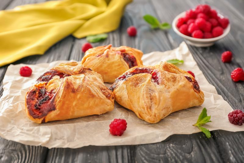 Parchment with delicious puff pastries. On wooden table royalty free stock photo