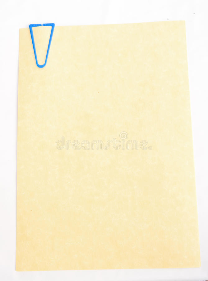 Parchment paper with blue paper clip. A sheet of good quality parchment left blank for messages is shown isolated with a blue paper clip stock photography