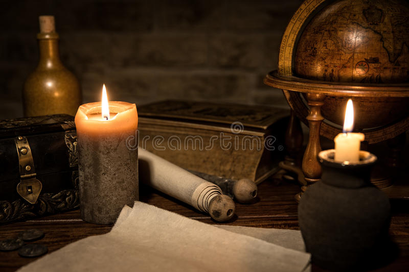 parchment paper, a old globe and candles, a old book and a wooden box, concept medieval background stock photo