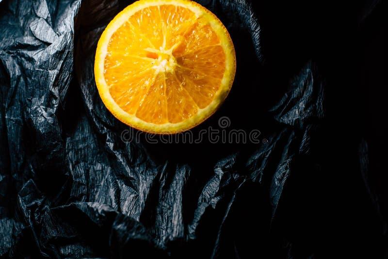 Parcialmente uma laranja em um fundo escuro imagem de stock royalty free