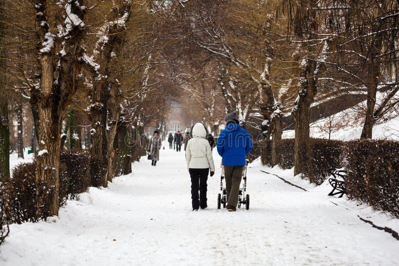 Parco della città nell'inverno Passeggiate giovani di una famiglia Mamma, papà e un passeggiatore con un piccolo bambino immagine stock libera da diritti
