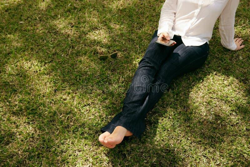 Parco di seduta mandante un sms dell'erba del telefono cellulare della donna dell'angolo alto immagini stock